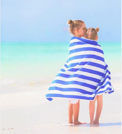 2 children stand on a beach with a blue and white striped towel wrapped around them